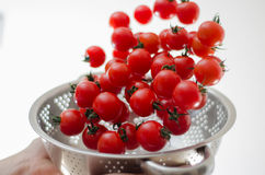 Cherry Tomatoes Tumbling Into Metal Colander Stock Photos