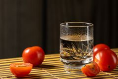 Cherry tomatoes and vodka on the mat home style stock images