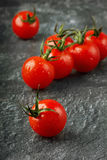 Cherry tomatoes in water drops. On the black granite surfaces Royalty Free Stock Photography