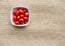 Cherry tomatoes in white bowl. On natural background royalty free stock image