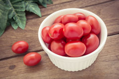 Cherry tomatoes in white bowl, vintage style light Royalty Free Stock Images
