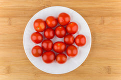 Cherry tomatoes in white glass plate on wooden table Stock Images