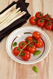 Cherry tomatoes in a white plate with asparagus Stock Photos