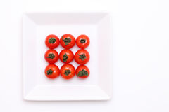 Cherry tomatoes on white plate. On white background Royalty Free Stock Photography