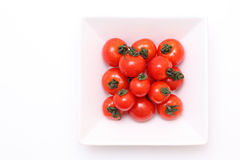 Cherry tomatoes on white plate. On white background Stock Images