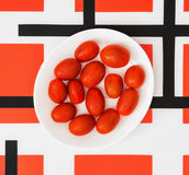 Cherry tomatoes on white plate and red geometric modern backgrou Stock Photos