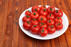 Cherry tomatoes on white plate on wooden background Stock Photo