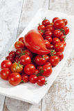 Cherry tomatoes in white wooden bowl Stock Photo