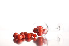 Cherry tomatoes and wine glass. A bunch of red cherry tomatoes lie on the surface and in a wine glass on its side.  Isolated on a white background with Stock Images