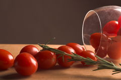 Cherry Tomatoes And A Wine Glass. Cherry tomatoes spilling out from a wine glass on it's side Stock Image