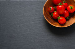 Cherry tomatoes in wooden bowl on black stone surface. Top view with copy space Royalty Free Stock Photos