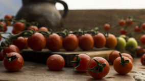 Cherry tomatoes on wooden chopping board and table. Royalty Free Stock Image