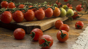 Cherry tomatoes on wooden chopping board and table. Stock Images