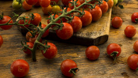 Cherry tomatoes on wooden chopping board and table. Royalty Free Stock Photography