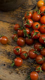 Cherry tomatoes on wooden chopping board and table. High resolution image Stock Images