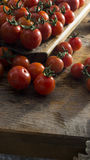 Cherry tomatoes on wooden chopping board and table. Royalty Free Stock Photo