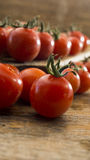 Cherry tomatoes on wooden chopping board and table. Royalty Free Stock Images
