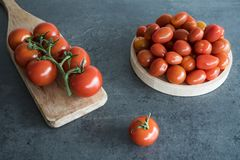 Cherry tomatoes on wooden plate and cutting board, stock photo