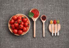 Cherry tomatoes in a wooden plate on a gray background. Adjika sauce, red and black pepper, parsley, mustard and pesto in spoons royalty free stock image