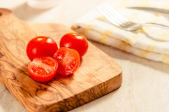 Cherry tomatoes on wooden stong. Ciligino tomatoes on olive wood cutting board with napkin and cutlery on white table Royalty Free Stock Photography