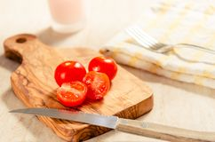 Cherry tomatoes on wooden stong. Ciligino tomatoes on olive wood cutting board with napkin and cutlery on white table Royalty Free Stock Image
