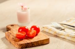 Cherry tomatoes on wooden stong. Ciligino tomatoes on olive wood cutting board with napkin and cutlery on white table Royalty Free Stock Photo