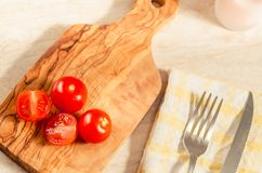 Cherry tomatoes on wooden stong. Ciligino tomatoes on olive wood cutting board with napkin and cutlery on white table Stock Images