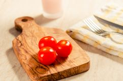 Cherry tomatoes on wooden stong. Ciligino tomatoes on olive wood cutting board with napkin and cutlery on white table Stock Photography