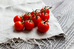 Cherry tomatoes on a wooden surface and homespun cloth with natu Stock Photo