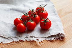 Cherry tomatoes on a wooden surface and homespun cloth Stock Image