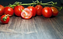 Cherry tomatoes on the wooden table. Fresh bush with cherry tomatoes on the wooden table in kitchen Royalty Free Stock Image