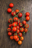 Cherry tomatoes on wooden table Stock Photos
