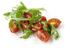 Cherry Tomatoes y Arugula aislados Imágenes de archivo libres de regalías