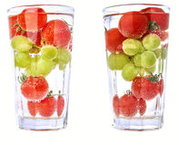 Cherry tomatos and grapes in a cocktail glas with water - isolated, two versions. Stock Photo
