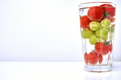 Cherry tomatos and grapes in a glas with waterwith copy space. Cherry tomatos and grapes in a glas with water and air bubbles Royalty Free Stock Photo