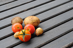 Cherry tomatos and potatos, on a wooden table Royalty Free Stock Photography