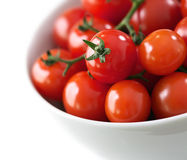 Cherry tomatos in a white bowl. Cherry tomatos on the vine in a white bowl royalty free stock photo