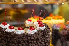 Cherry Topped Chocolate Cake in Window Display Stock Photography