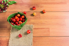Cherry varieties in Thailand in a banana leaf krathong Placed on the Brown wooden tables. Cherry red with orange. Sour and a little sweet. It is very Stock Image