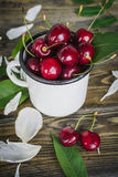 Cherry in the white cup. On wooden background Royalty Free Stock Photos