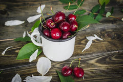Cherry in the white cup. On wooden background Royalty Free Stock Image