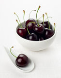 Cherry white spoon, cherries group white bowl. Single cherry on a white china spoon and a ripe group cherries in a small round white bowl stock photography