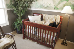 Cherry wood baby crib in nursery interior. Stock Image