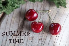Cherry on a wooden background with the inscription stock photography