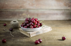 Cherry on a wooden background. Sweet cherry in a plate on a wooden background stock photos