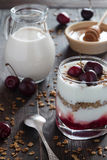 Cherry yoghurt in a glass with muesli, milk and honey Royalty Free Stock Images
