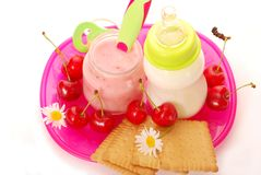 Cherry yogurt and bottle of milk for baby. Jar with  cherry yogurt ,bottle of milk and biscuits as baby food Stock Photos
