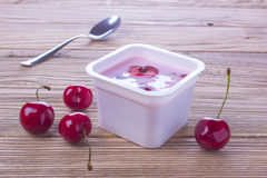 Cherry yogurt in plastic box with spoon Royalty Free Stock Image