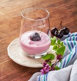 Cherry yogurt and ripe cherry with a sprig of Royalty Free Stock Photo