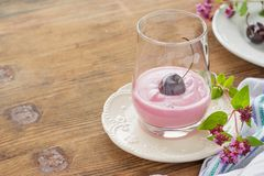 Cherry yogurt and ripe cherry with a sprig of Stock Photos
